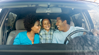 Smiling African family inside the car